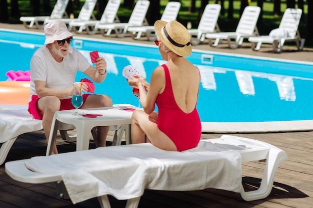 Slim donna in pensione che indossa il costume da bagno rosso giocando a carte con il suo divertente marito
