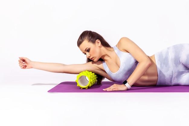Donna sportiva esile che massaggia le mani e allevia la tensione usando il rullo fitness sdraiato sul tappetino da yoga