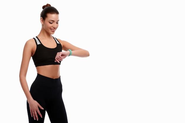 Slim forte donna caucasica in abiti sportivi controllare orologi intelligenti su sfondo bianco isolato