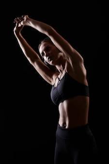 Sportiva muscolare forte e sottile che si estende prima dell'allenamento e ascoltare musica. uno stile di vita sano.