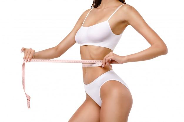 Il corpo sottile della donna abbronzata su sfondo grigio - misurazione della vita