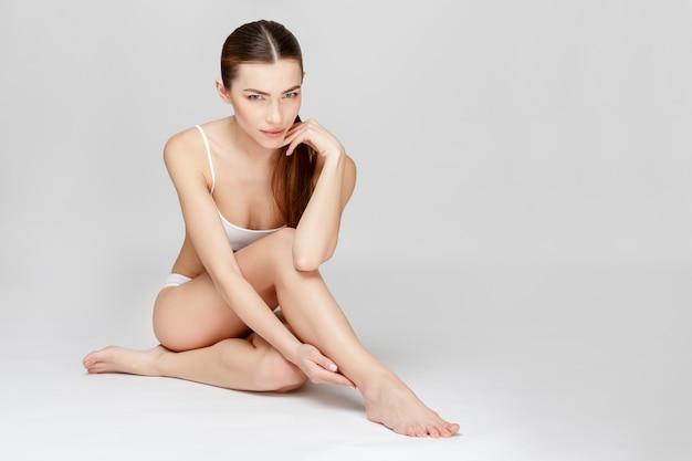 Sottile corpo abbronzato da donna su grigio