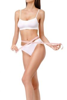 Corpo di donna abbronzata sottile sul muro bianco - misurazione della vita