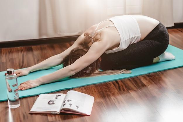 Donna sottile che fa esercizi di pilates mentre era seduto su una stuoia di yoga verde sul pavimento a casa. sport di stretching. yoga a casa