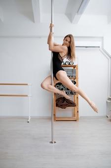 Donna esile sulla formazione di pole dance in classe.