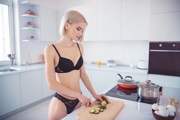Slim donna in posa nella sua lingerie in cucina