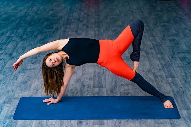 Donna esile nella posa della plancia laterale alla lezione di yoga, esercizio di vasisthasana femmina in equilibrio sul tappetino al chiuso in palestra per il fitness