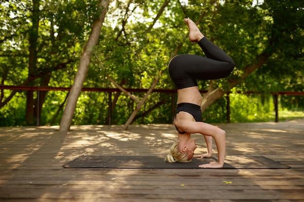 Donna esile si leva in piedi sulla sua testa, esercizio di equilibrio, allenamento yoga nel parco estivo. meditazione, lezione in forma sull'allenamento all'aperto