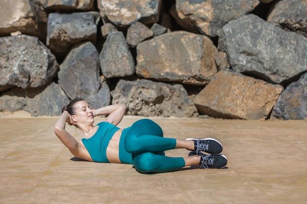 Slim donna torcendo il corpo durante l'allenamento