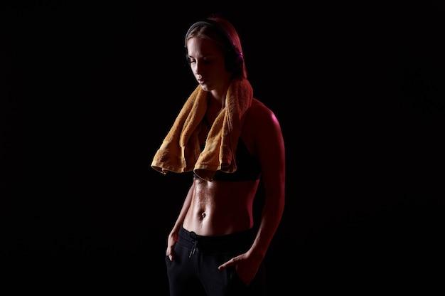 Donna esile con corpo muscoloso che tiene asciugamano sul collo dopo l'allenamento. forte sportiva con le cuffie su sfondo nero