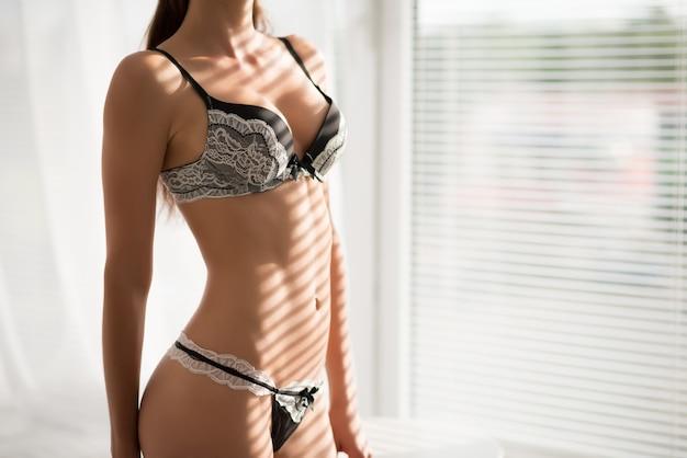 Giovane donna castana esile in biancheria intima sexy in bianco e nero