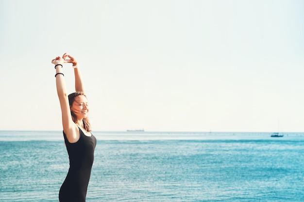 Giovane modella esile in abito nero sullo sfondo del mare o del lago di montagna
