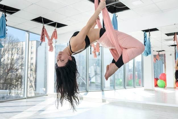 Giovane donna esile che fa esercizi rilassanti di yoga della mosca nella palestra di addestramento di forma fisica tutto per uno stile di vita sano