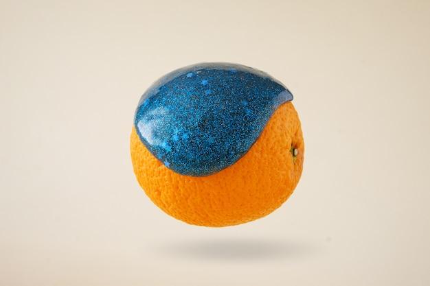 Gli schizzi di macchie di melma avvolgono l'arancione arancione, concetto contemporaneo di cibo per levitazione
