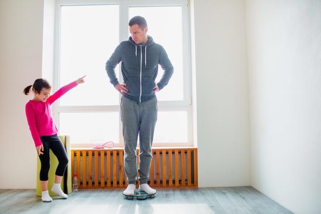 Dimagrante. padre e figlia vengono pesati su bilance domestiche da interni. momenti divertenti e gioiosi divertendosi in famiglia. dieta, corretta alimentazione e concetto di stile di vita sano.