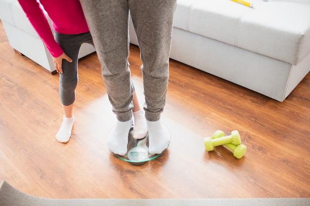 Dimagrante. padre e figlia vengono pesati su bilance domestiche da interni