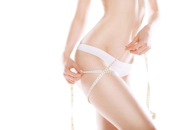 Donna dimagrante che misura la sua coscia con nastro di misurazione su sfondo bianco