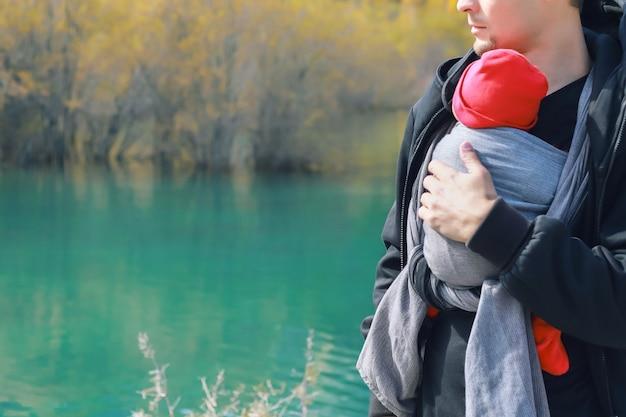 Imbracatura all'aperto l'uomo sta portando il suo bambino e viaggia nel lago di montagna autunnale concetto di babywearing