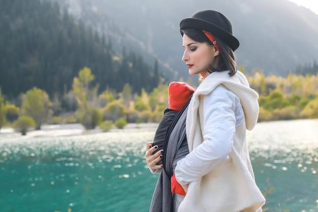 Imbracatura all'aperto la madre sta portando il suo bambino e viaggia nel lago di montagna autunnale concetto di babywearing