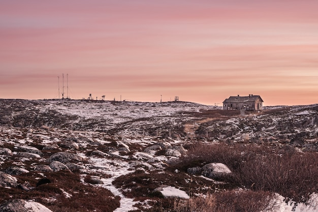 Percorso sdrucciolevole per una stazione meteorologica abbandonata su una collina. l'aspro paesaggio serale polare. russia.