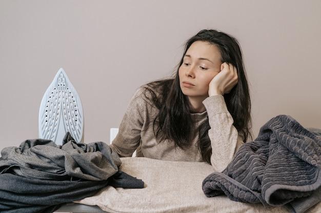 Una ragazza sciatta non ama accarezzare. depressione in una casalinga. sconvolta la donna dalla pulizia quotidiana, stiratura e disinfezione. mamma stanca che accarezza le cose
