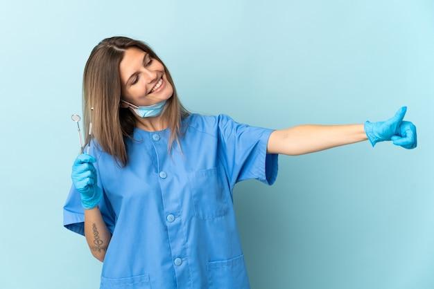 Dentista slovacco tenendo gli strumenti isolati su sfondo blu dando un pollice in alto gesto