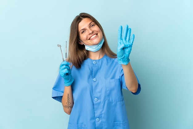 Dentista slovacco in possesso di strumenti isolati su sfondo blu felice e contando quattro con le dita