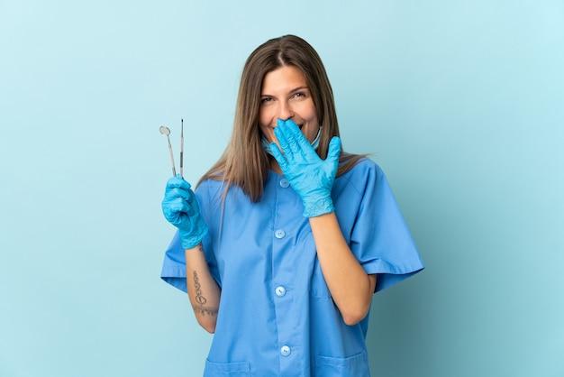 Dentista slovacco che tiene gli strumenti isolati su sfondo blu felice e sorridente che copre la bocca con la mano
