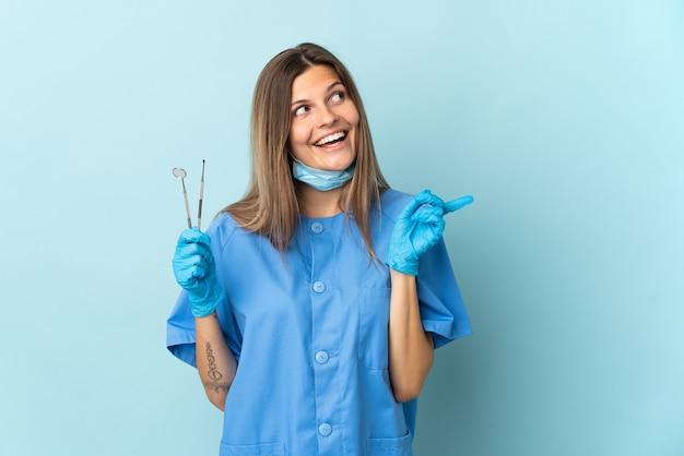 Il dentista slovacco tiene gli strumenti isolati su sfondo blu con l'intenzione di realizzare la soluzione sollevando un dito