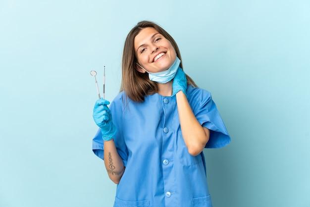Dentista slovacco che tiene gli strumenti isolati su sfondo blu ridendo