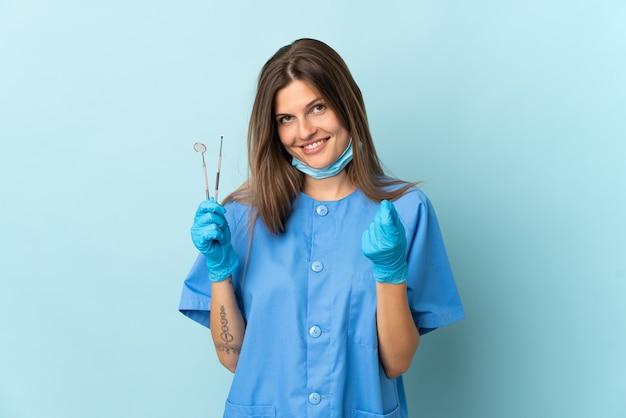 Strumenti di tenuta del dentista slovacco isolati su fondo blu che fanno gesto dei soldi money