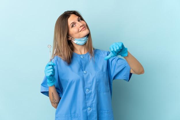 Dentista slovacco che tiene gli strumenti isolati su sfondo blu orgoglioso e soddisfatto di sé