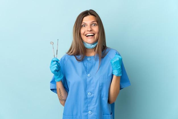Dentista slovacco che tiene gli strumenti isolati sulla parete blu che celebra una vittoria nella posizione del vincitore