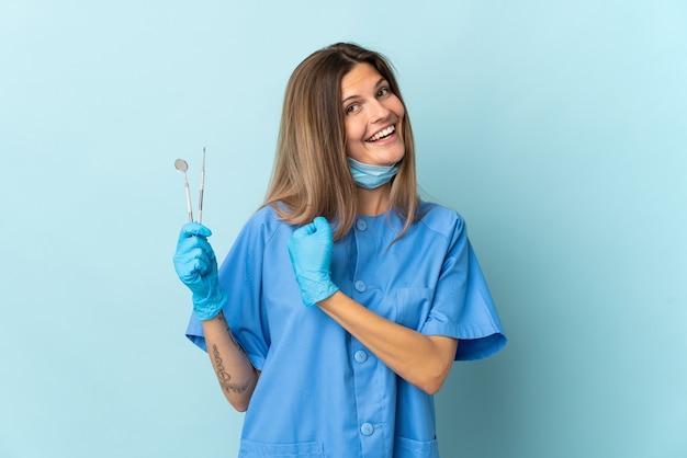 Dentista slovacco che tiene gli strumenti isolati sulla parete blu che celebra una vittoria