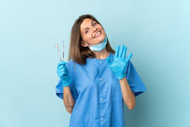 Dentista slovacco che tiene gli strumenti isolati sulla parete blu che saluta con la mano con l'espressione felice