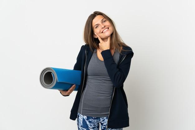 Ragazza slovacca che va alle lezioni di yoga isolate sulla parete bianca felice e sorridente