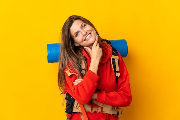 Donna slovacca dell'alpinista con un grande zaino isolato sulla parete gialla felice e sorridente