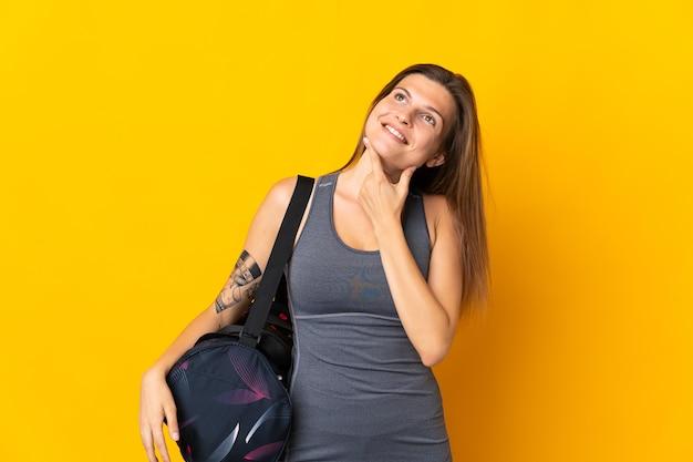 Donna sportiva slovacca con borsa sportiva isolata su sfondo giallo, alzando lo sguardo mentre sorride