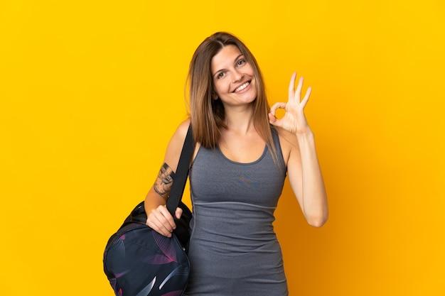 Donna sportiva slovacca con borsa sportiva isolata su sfondo giallo che mostra segno ok con le dita