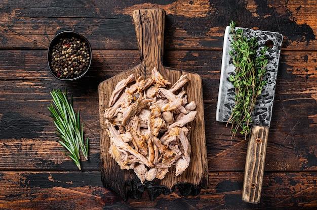 Carne di maiale soffiata a cottura lenta su una tavola di legno con mannaia da macellaio. legno scuro