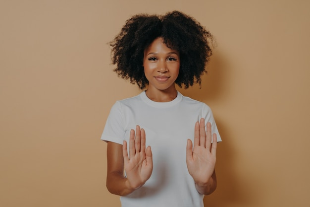 Rallentare. giovane donna di razza mista sorridente con acconciatura riccia alzando i palmi in stop o gesto di divieto e dicendo di no mentre si trovava vestita con una maglietta bianca sul muro marrone dello studio