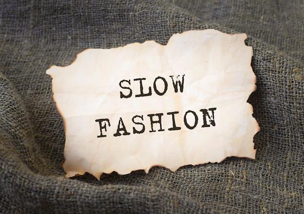 Iscrizione di moda lenta sulla vecchia carta vintage. movimento sostenibile.