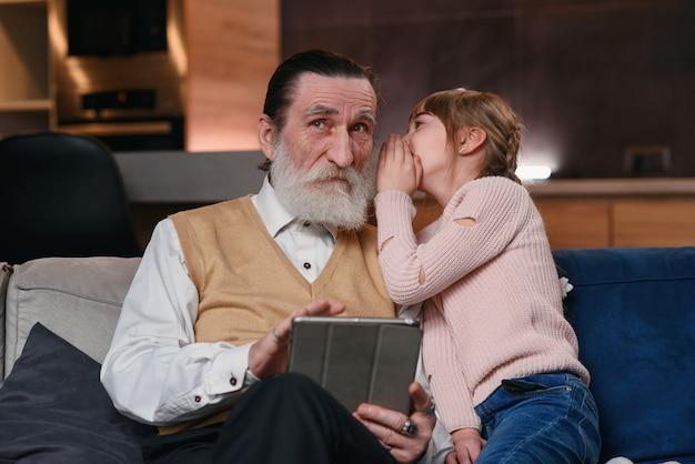 Rallentatore di una ragazza carina e allegra con trecce divertenti che sussurra all'orecchio del nonno il suo segreto mentre si siedono insieme sul divano di casa
