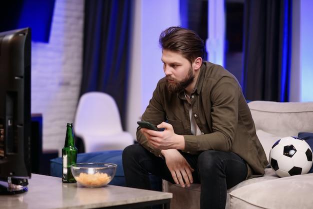 Rallentatore di un bell'uomo moderno di 30 anni con la barba che è seduto davanti alla tv e guarda periodicamente partite di calcio e app sul suo cellulare mentre beve birra