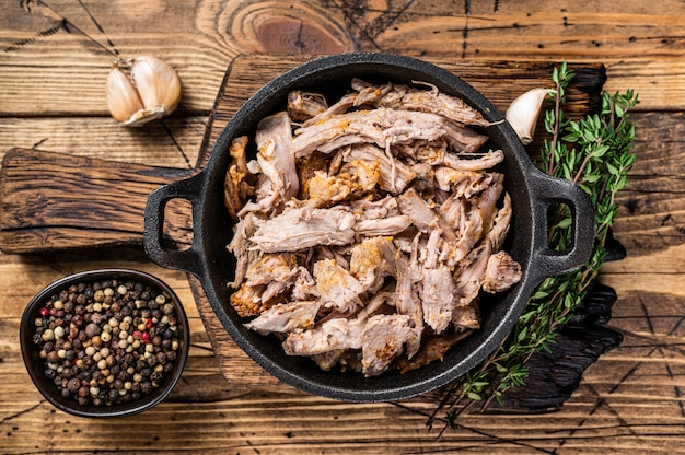 Carne di maiale sfogliata a listarelle lenta in padella con coltello da macellaio. in legno