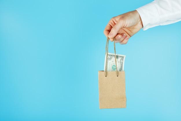 Una borsa per piccoli aiuti fatta di carta in una mano tesa con dollari usa su sfondo blu. layout del modello di packaging con spazio per la copia, la pubblicità.