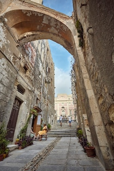 Piccolo vicolo nel centro storico di cagliari durante il giorno dove un signore
