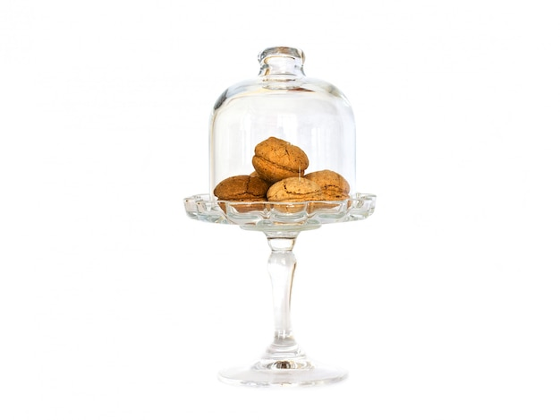 Piccoli biscotti di mandorle in un vaso di vetro su una gamba alta sotto un bicchiere