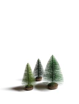 Piccoli alberi di natale artificiali isolati su sfondo bianco. orientamento verticale.