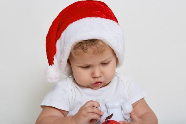 Piccolo bambino attraente che indossa in cappello di babbo natale, bambino che guarda il giocattolo nelle sue mani con interesse, sembra curioso, con i capelli mossi, in posa isolato sopra il muro bianco.